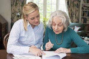 Kvinna hjälper dam att teckna en fullmakt