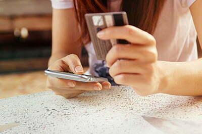 En kvinna använder rikskuponger med app och betalkort